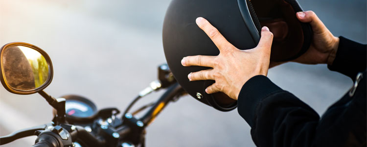 Man holding helmet preparing to mount motorcycle